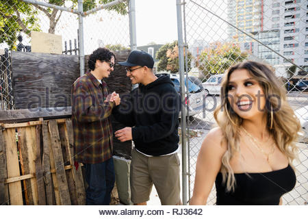 Latinx male friends shaking hands at urban gate - Stock Photo