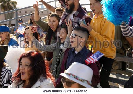 Enthusiastic Latinx baseball fans cheering in bleachers - Stock Photo