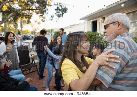 Latinx senior couple dancing on patio - Stock Photo