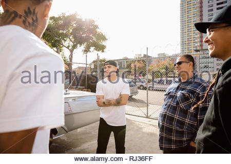 Latinx men friends talking, hanging out in urban parking lot - Stock Photo