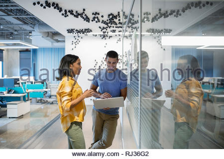 businessman and businesswoman with laptop working in modern office - Stock Photo