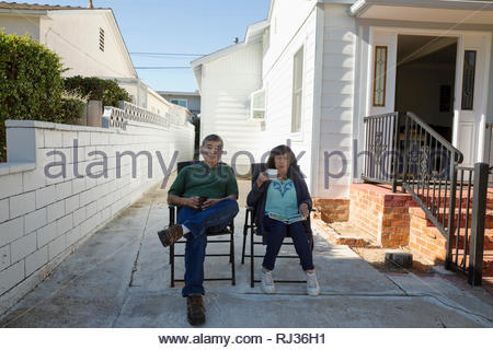 Portrait senior Latinx couple sitting in driveway drinking coffee - Stock Photo
