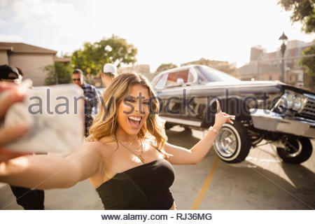 Confident, enthusiastic Latinx young woman taking selfie in front of low rider car bouncing in parking lot - Stock Photo