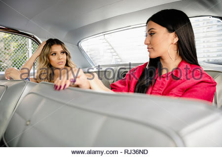 Latinx young women friends talking in back seat of vintage car - Stock Photo