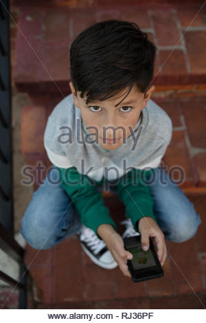 Portrait from above Latinx boy using smart phone on steps - Stock Photo