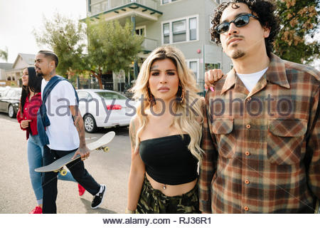 Latinx couples with skateboard crossing street - Stock Photo
