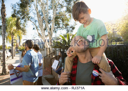 Latinx father carrying son on shoulders, canvassing voters in neighborhood - Stock Photo