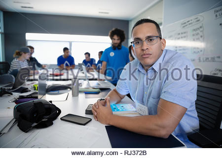 Portrait confident male computer programmer with virtual reality simulator in conference room - Stock Photo