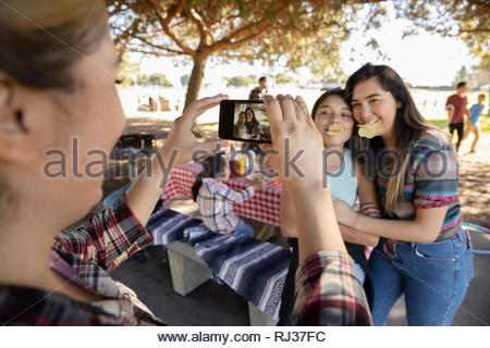 Woman with camera phone photographing playful girls in park - Stock Photo
