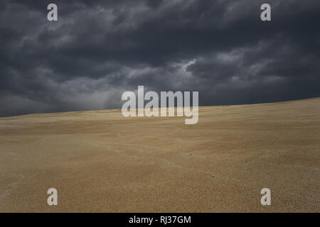 Cloudy sand sea dune before storm from a large beach. North of Portugal. Enhanced sky. - Stock Photo