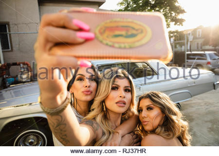 Latinx young women friends taking selfie with camera phone in front of low rider car in parking lot - Stock Photo