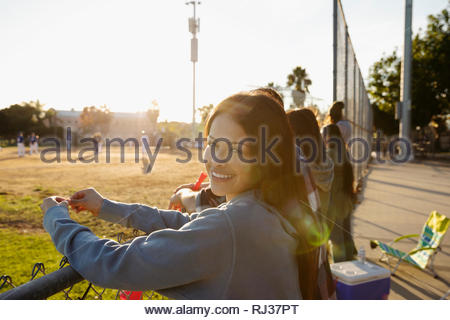 Portrait smiling, confident Latinx young woman watching baseball game - Stock Photo