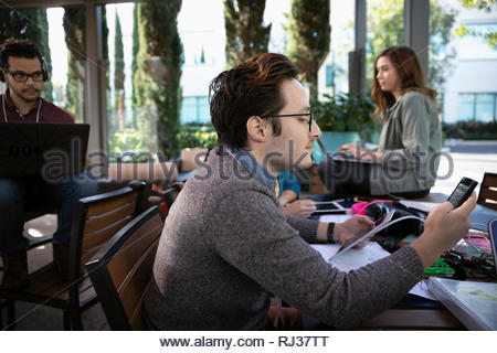 businessman working, using smart phone and digital tablet in cafe - Stock Photo