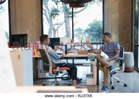 businessmen talking and eating pizza in open plan office - Stock Photo