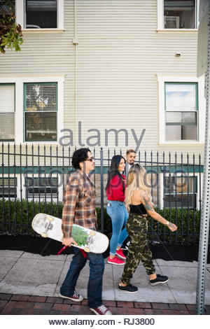 Latinx friends with skateboard walking on neighborhood sidewalk - Stock Photo
