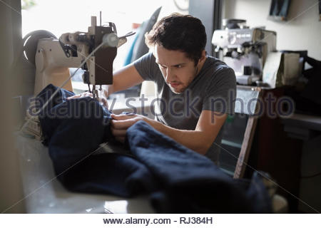 Focused male tailor using sewing machine in denim repair shop - Stock Photo