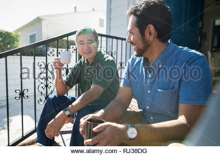 Latinx son and senior father drinking coffee on sunny front stoop - Stock Photo