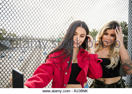 Latinx young women friends taking selfie with camera phone at overpass fence - Stock Photo