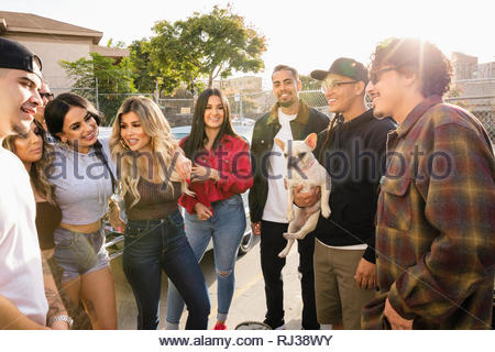 Latinx friends with French bulldog hanging out in sunny parking lot - Stock Photo