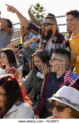 Excited fans cheering in bleachers at baseball game - Stock Photo