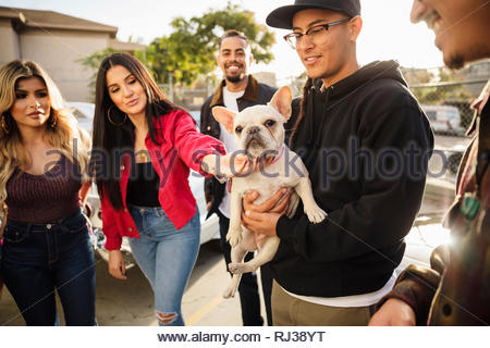 Latinx friends with French bulldog hanging out - Stock Photo