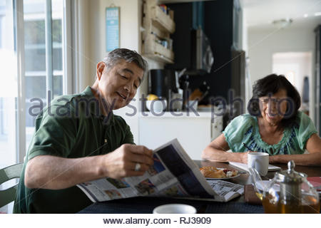 Latinx senior couple reading newspaper and eating breakfast at kitchen table - Stock Photo