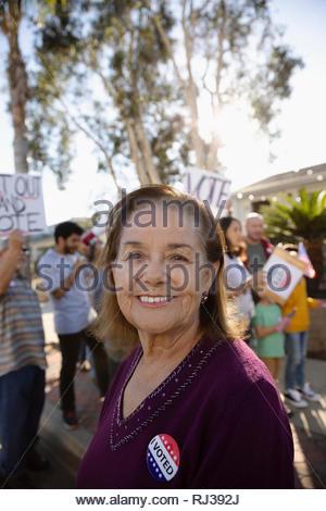 Portrait confident Latinx senior woman volunteering, canvassing voters - Stock Photo