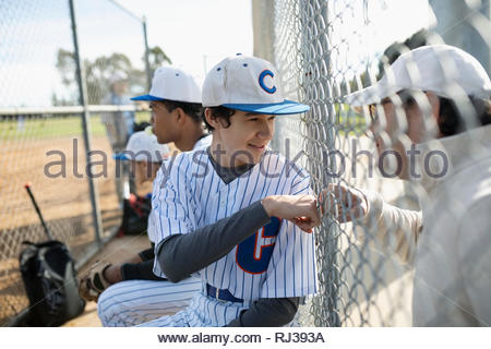 Baseball player fist bumping dad at fence - Stock Photo