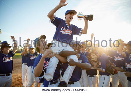 Excited baseball team celebrating, carrying player with trophy on shoulders - Stock Photo