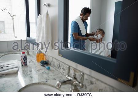 Latinx son shaving senior father s face in bathroom - Stock Photo