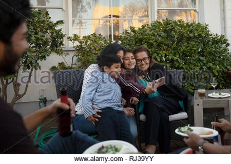 Latinx multi-generation family taking selfie on patio - Stock Photo