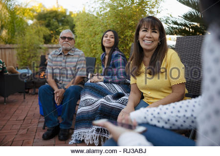 Latinx multi-generation family talking on patio - Stock Photo