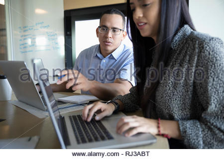 businessman and businesswoman using laptops in conference room meeting - Stock Photo