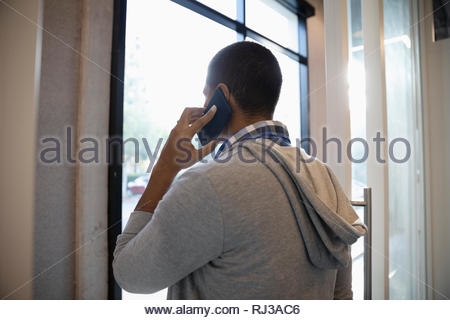 Man talking on cell phone at window - Stock Photo