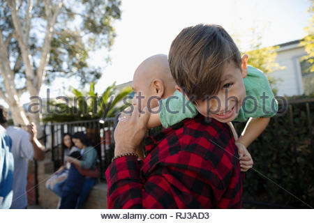Latinx father carrying happy son over shoulders - Stock Photo