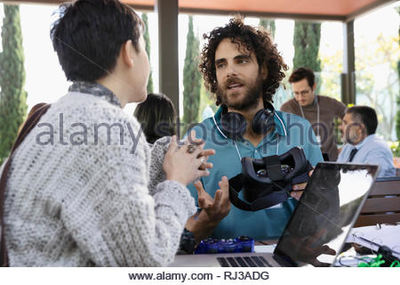 Computer programmers with virtual reality simulator talking in office - Stock Photo