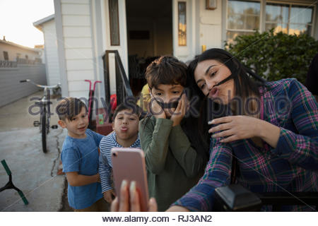Playful Latinx mother and sons taking selfie - Stock Photo