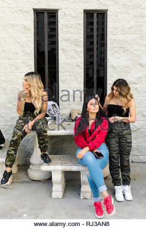 Latinx young women friends hanging out - Stock Photo