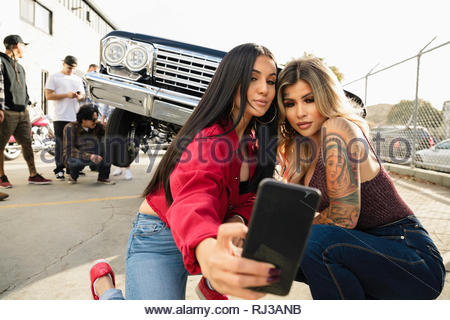 Latinx young women taking selfie in front of low rider on urban street - Stock Photo