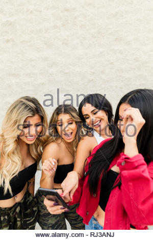 Latinx young women friends hanging out, using smart phone - Stock Photo