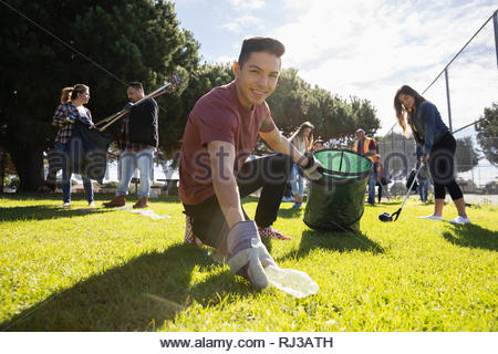 Portrait confident Latinx young male volunteer picking up garbage in sunny park - Stock Photo