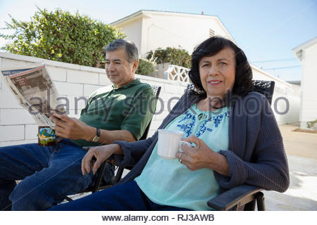 Portrait Latinx senior couple reading newspaper and drinking coffee in driveway - Stock Photo