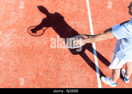 High angle view of mature man serving tennis ball on red court - Stock Photo