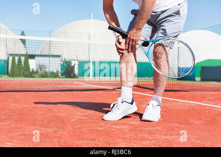 Low section of mature man holding tennis racket while suffering from knee pain on red tennis court during summer - Stock Photo
