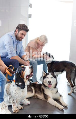 Pet owners waiting with dogs at veterinary clinic - Stock Photo