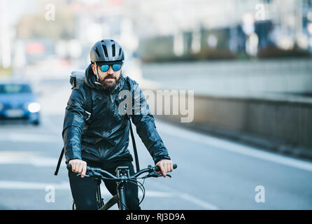 A front view of male bicycle courier delivering packages in city. Copy space. - Stock Photo