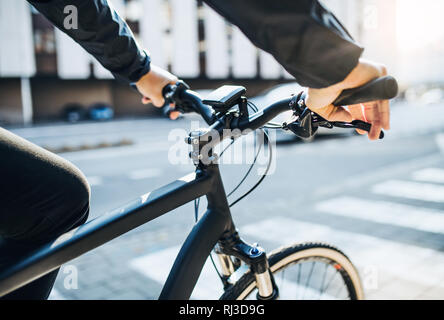 A midsection of businessman commuter with electric bicycle traveling to work in city. - Stock Photo