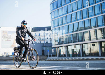 A male bicycle courier delivering packages in city. Copy space. - Stock Photo