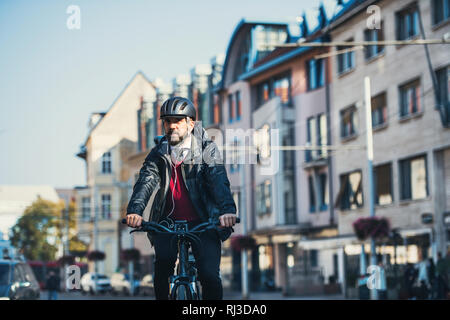 Hipster businessman commuter with electric bicycle traveling home from work in city. - Stock Photo
