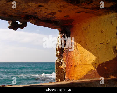 Tranquil view of summer ocean waves of blue sea water, through eroded stone hole formation in orange warm colored rock wall by the sea. - Stock Photo